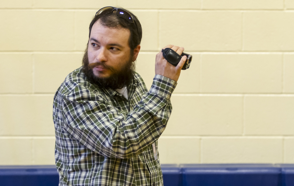 James Barron of Lewiston videotapes Portland voters at East End Community School as they sign a petition to require background checks on gun sales.