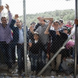 Migrants and refugees wait outside the Moria camp on the Greek island of Lesbos in October. Congress and many governors are putting pressure on the Obama administration to demonstrate that its screening process for refugees is adequate to protect Americans. 2015 Associated Press file photo