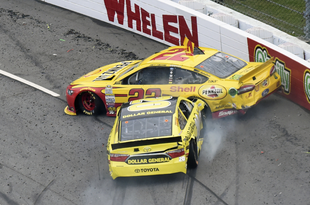 Joey Logano (22) and Matt Kenseth (20) tangle in Turn 1 during the NASCAR Sprint Cup Series auto race Sunday at Martinsville Speedway in Martinsville, Va. The Associated Press