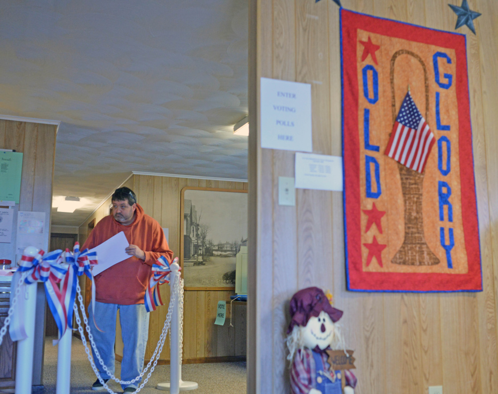 A voter carries his ballot at the Anson Town Office Tuesday. Voters backed changing the tax collector from an elected to an appointed position, and also enacted a recall ordinance.