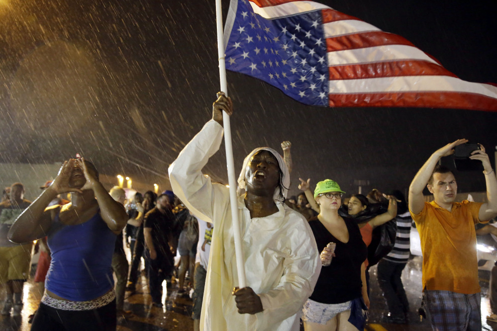 In this Sunday, Aug. 9, 2015, file photo, protesters march to mark the one-year anniversary of Michael Brown being shot and killed by Ferguson Police Officer Darren Wilson.