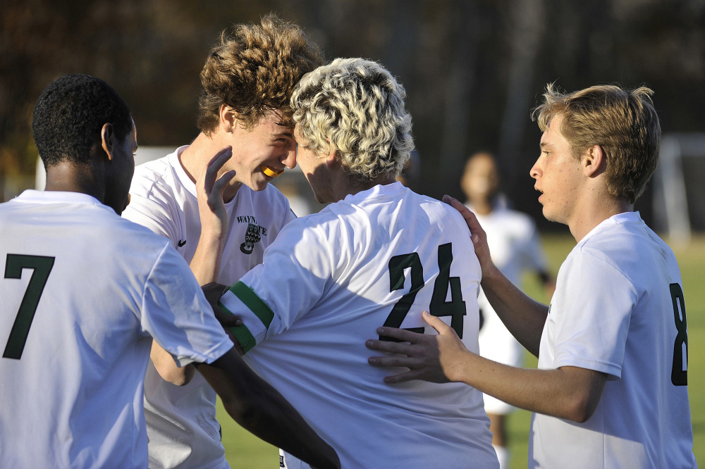 Ilyas Abdi (7), Tommy Silk (8), and Cullen Bollinger congratulate senior Aaron Lee on his goal during the second half of Waynflete's 4-0 win over Monmouth in the Class C South boys' soccer regional final in Portland on Wednesday. (Photo by John Ewing/Staff Photographer)
