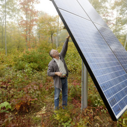 Dan Burr demonstrates how he changes the angle of the solar panel at his Damariscotta home. (Photo by Shawn Patrick Ouellette/Staff Photographer)