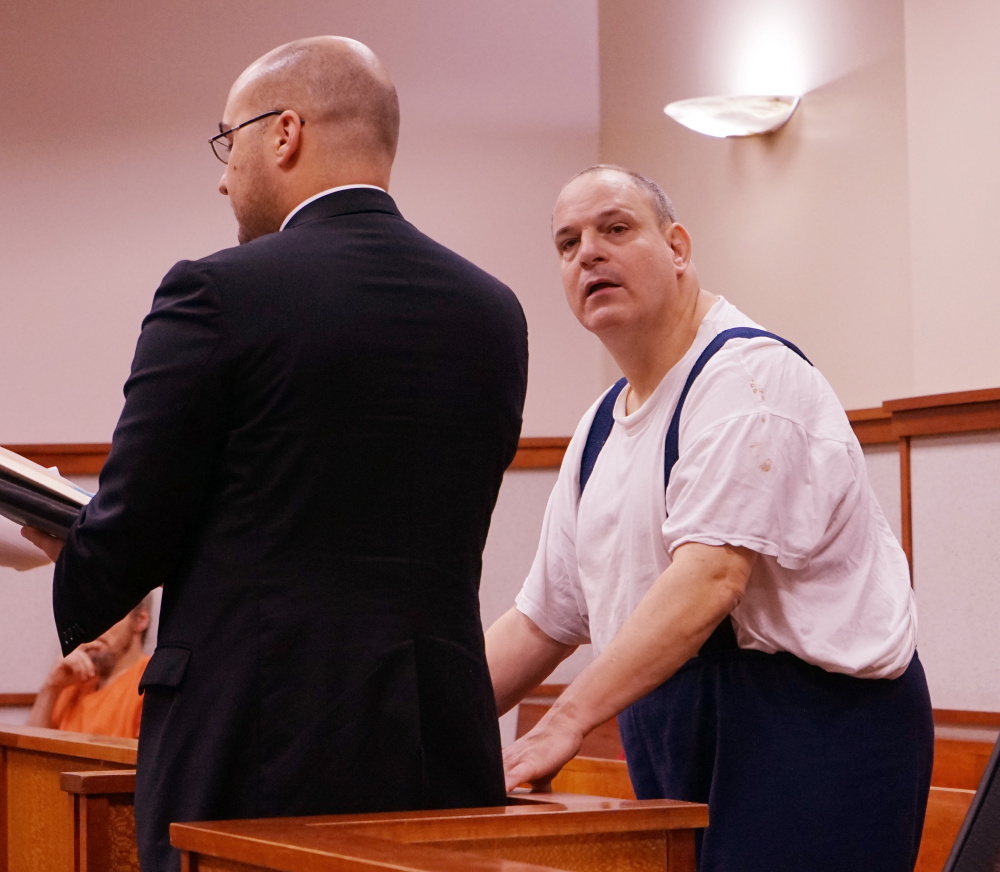 Steven Ricci, right, with his attorney, Mark Bullock, accepts new probation conditions in advance of his release from prison, in the Cumberland County Courthouse in Portland on Thursday.