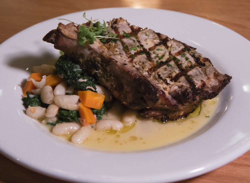 Grilled pork chop, served with cannellini beans, mustard greens and dijon.