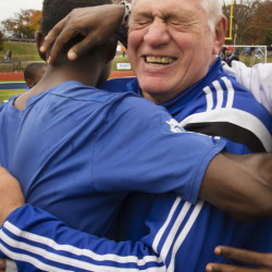 Lewiston Coach Mike McGraw, finishing his 33rd season with the Blue Devils, embraces his players after winning the state championship for the first time.