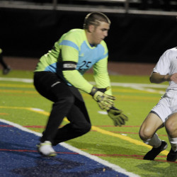 Walter Conrad slips the ball past Erskine Academy keeper Denver Cullivan for the first goal of the game Saturday, starting Yarmouth on its way to a 3-0 win in the Class B boys' soccer state championship game at Fitzpatrick Stadium.