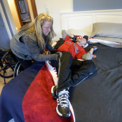 Carrie Walker helps her husband, Brian, who was paralyzed after a four-wheeler accident, as he gets in bed to work on some exercises to strengthen his neck and shoulders at his Portland home last December.