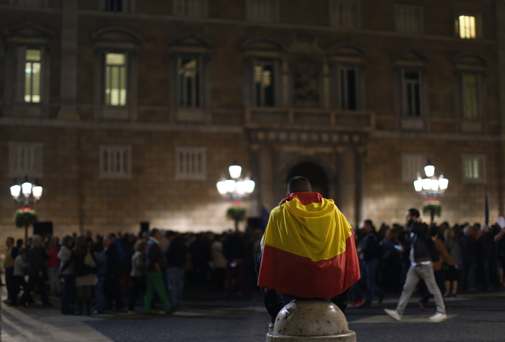 """A man wraps himself in a Spanish flag during a demonstration calling for the """"unity of Spain"""" in Barcelona on Thursday."""