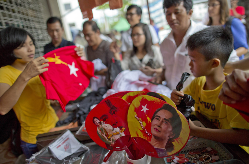 "People gather to buy merchandise with pictures of opposition leader Aung San Suu Kyi at a shop run by her National League of Democracy party in Yangon, Myanmar, on Tuesday. Her party, which appears headed for a massive election victory, accused the government election panel Tuesday of intentionally delaying results, saying it may be trying ""to play a trick."" (The Associated Press)"