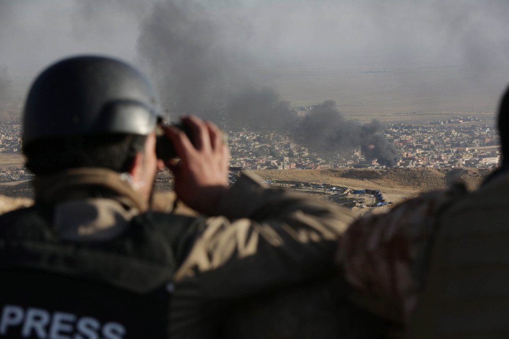 A journalist watches as smoke rises over Sinjar in northern Iraq from oil fires set by Islamic State militants as Kurdish Iraqi fighters, backed by U.S.-led airstrikes, launch a major assault on Thursday.