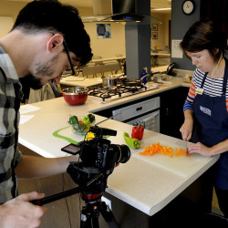 Videographer Patrick Gill shoots a closeup of Kate McCarty prepping peppers for a video to be posted on YouTube.