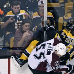 Bruins fans watch as defenseman Dennis Seidenberg, in his first game since having back surgery in the off-season, is slammed into the boards by Avalanche left wing Cody McLeod in the first period of Thursday night's game in Boston. Seidenberg returned to the ice.