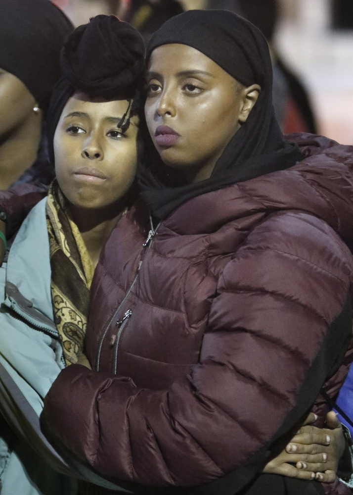 Naj Abdullahi, left, and Ifrah Hassan listen to a speaker during Friday night's rally in Monument Square. Abdullahi is a sophomore at Waynflete School in Portland and Hassan is a junior at Deering High.