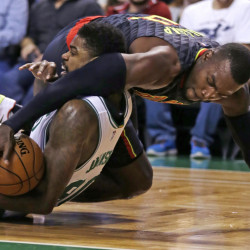 Atlanta forward Paul Millsap, top, tries to strip the ball from the grip of Celtics forward Amir Johnson as they hit the floor in the first quarter of Friday night's game in Boston.