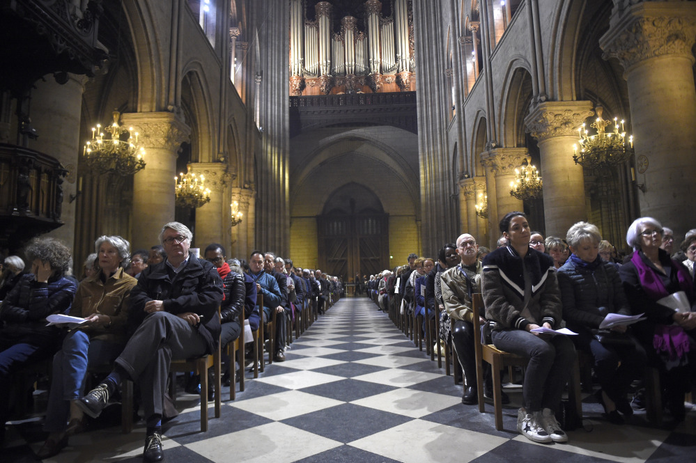 People attend a mass in homage to terrorist attack victims at the Notre Dame cathedral in Paris Sunday.