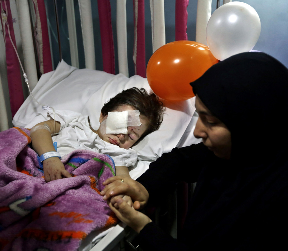 Adraa Taleb holds the hand of her 3-year-old cousin, who was wounded last week in suicide bombings in a Beirut suburb that killed at least 43. Some ask why the attacks there didn't get the same attention as those in Paris.