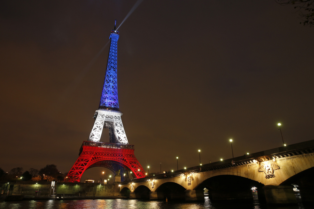 The Eiffel Tower is bathed in floodlights displaying the colors of the French flag Monday as thousands gathered there and in the Place de la Republique square around memorials to the victims of Friday's attacks.