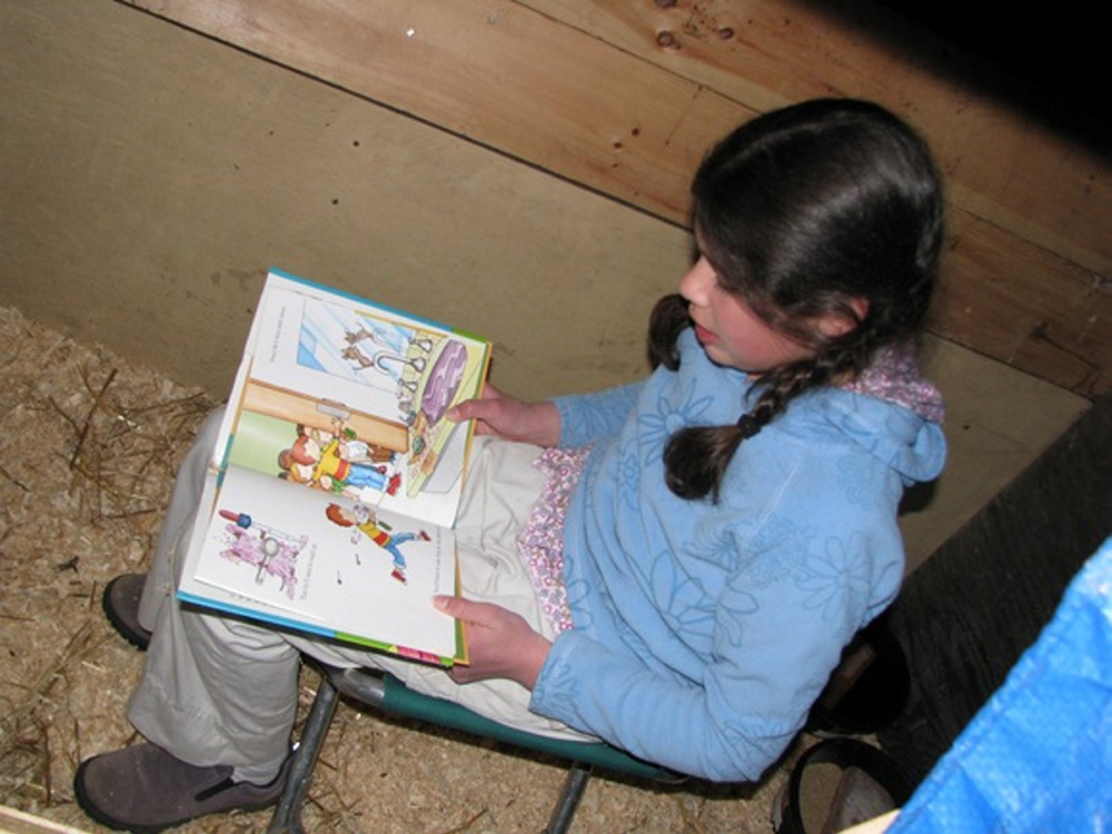 Lucia, 10, reads to her pigs.