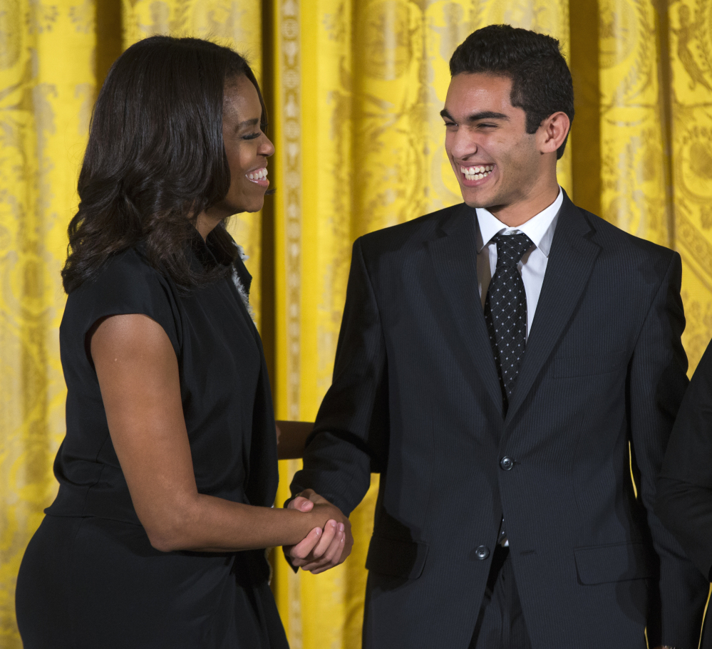 First lady Michelle Obama shakes hands with Ibrahim Shkara of The Telling Room in Portland, Maine, during the 2015 National Arts and Humanities Youth Program Awards on Tuesday at the White House in Washington.
