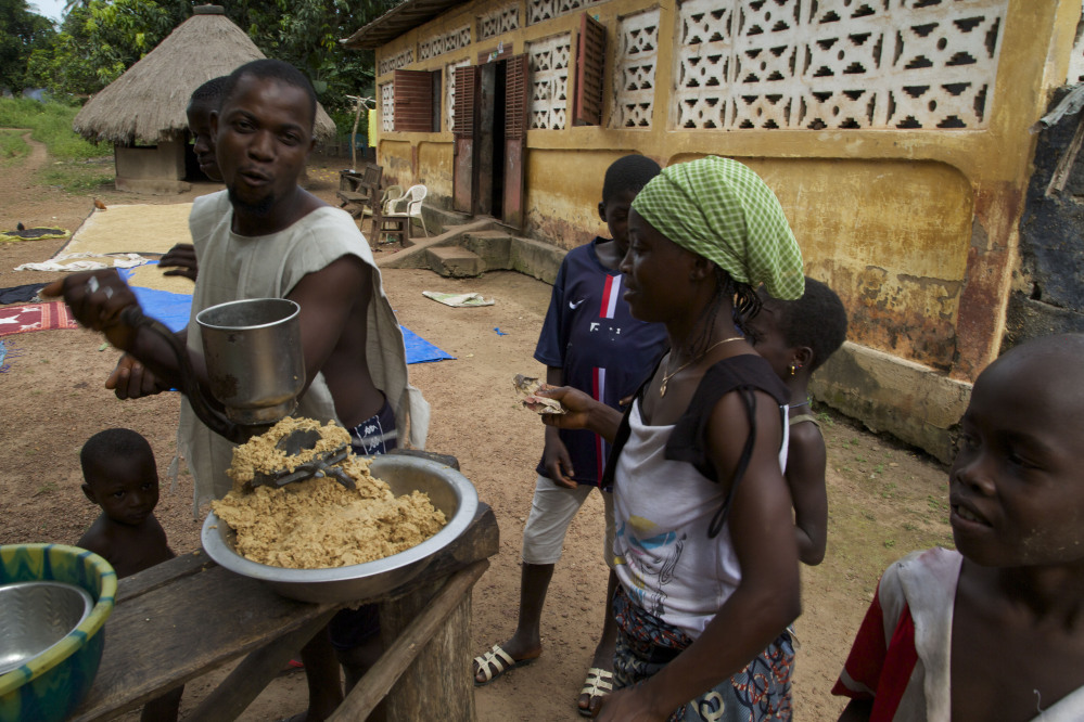 A man, left, grinds peanuts into a mash to sell to people in the village of Tanah, Guinea. West Africa's Ebola outbreak is down to a handful of cases and they are all in Guinea where the disease first emerged nearly two years ago and where health workers battle community resistance in their bid to extinguish the disease. The Associated Press