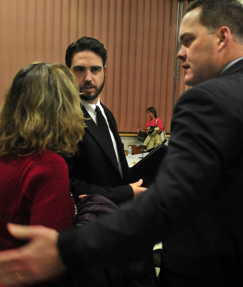 Don Reiter, center, is consoled by a woman and his lawyer, Gregg Frame, following Monday's vote by the Board of Education to fire him as principal of Waterville Senior High School.