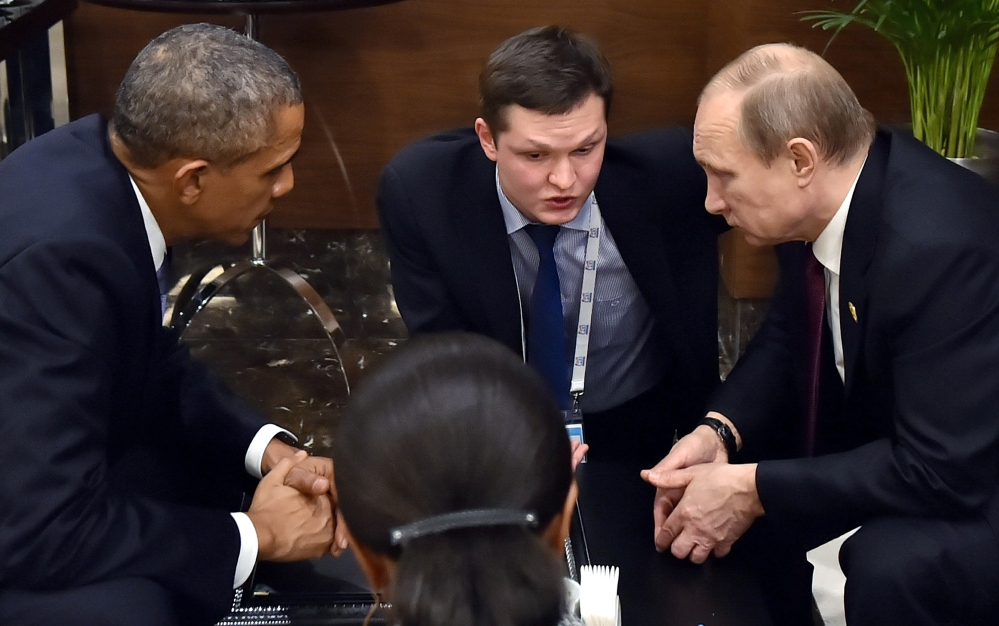 In this Sunday, Nov. 15, 2015, file photo, U.S. President Barack Obama, left, speaks with Russian President Vladimir Putin, right prior to the opening session of the G-20 summit in Antalya, Turkey.