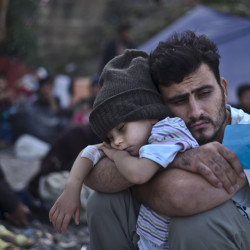 A Syrian refugee holds his sleeping child Oct. 4, after arriving on a dinghy from the Turkish coast to Greece. Despite last week's tragic events, France is sticking by its pledge to take in 30,000 Syrian refugees – while President Obama's plan to accept 10,000 is encountering massive resistance in the U.S.