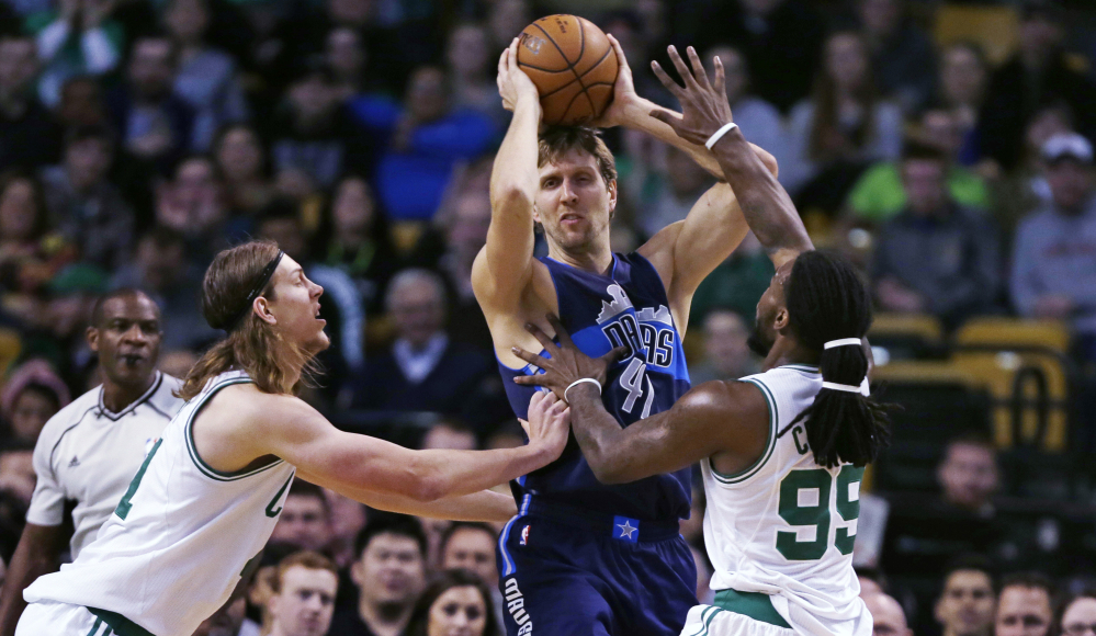 Dallas Mavericks forward Dirk Nowitzki, center, looks to pass while double-teamed by Celtics center Kelly Olynyk and forward Jae Crowder in the first quarter of the Mavericks' win Wednesday night in Boston. Nowitzki scored 23 points as Dallas won its fifth straight game. The Associated Press