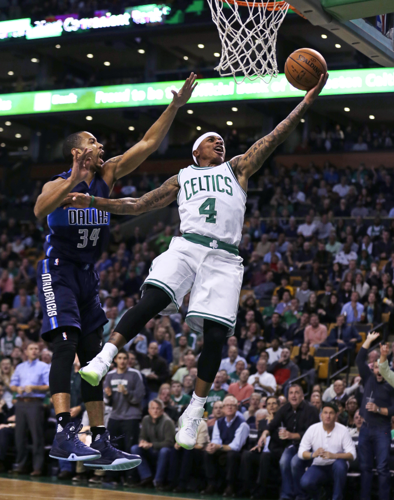 Celtics guard Isaiah Thomas flies past Mavericks guard Devin Harris on a layup in the first quarter. Boston's three-game winning streak ended with a 106-102 loss to Dallas.