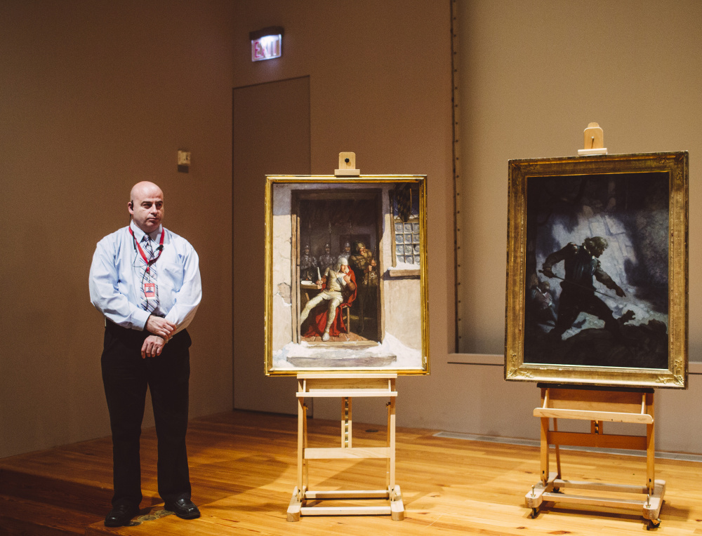 Portland Museum of Art security officer Shawn Higgins stands with two N.C. Wyeth paintings during a news conference Thursday announcing their recovery by the FBI. Wyeth is the father of Andrew Wyeth, one of the best-known American artists of the mid-20th century. The value of the two paintings is unclear.