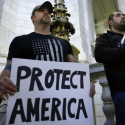Army veteran Jim Purcell of Burrillville, R.I., front left, displays a placard as Navy veteran Robert Martinez, right, holds a folded American flag during a rally Thursday at the Statehouse in Providence, R.I. The demonstrators oppose allowing Syrian refugees to enter Rhode Island following the terror attacks in Paris.