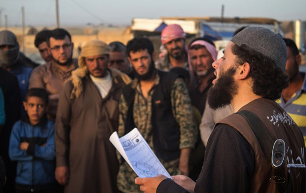 In photo from a militant website, a member of the Islamic State's vice police, right, reads a verdict handed down by an Islamic court in Raqqa, Syria. Some analysts expect the Islamic State to launch more attacks abroad to divert attention from its recent losses.