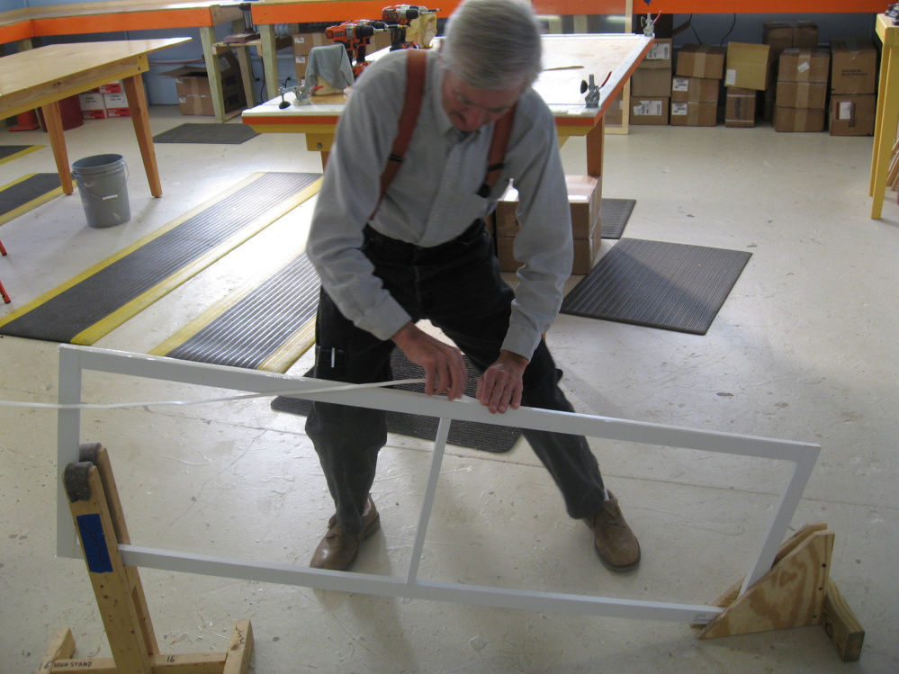 The humble Farmer helps build a reusable interior storm window at the Rockland plant of the nonprofit Window Dressers.