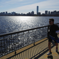 A jogger runs across Harvard Bridge past the Boston skyline in Cambridge, Mass. The state capital fared well in a real estate analysis that found a widening economic gap in neighborhoods in most U.S. cities.