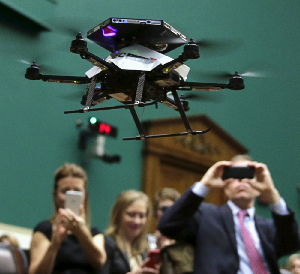 People photograph a drone during a demonstration at a House subcommittee meeting in Washington on Thursday. The FAA must find a way to streamline and adapt registration for a technology it never envisioned.