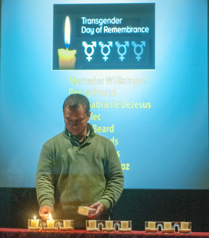 After reading a page of names of murder victims, Matthew Francis lights a candle during a transgender memorial event at the Holocaust and Human Rights Center of Maine at the University of Maine at Augusta.