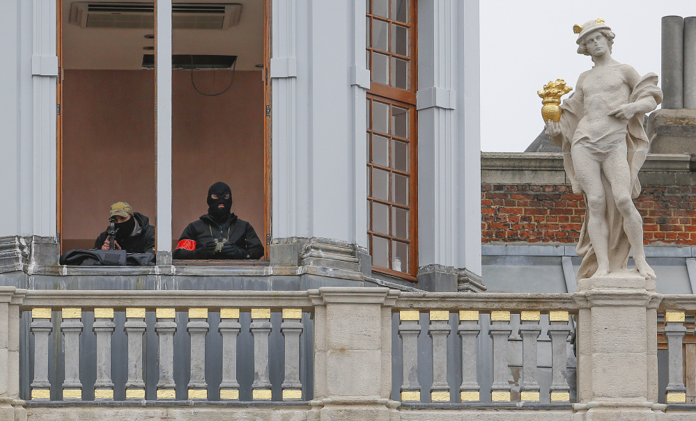 A sniper and an observer of the Belgian police special forces keep watch from the balcony of a building on Brussels Grand Place on Friday after security was tightened in Belgium following the fatal terror attacks in Paris.