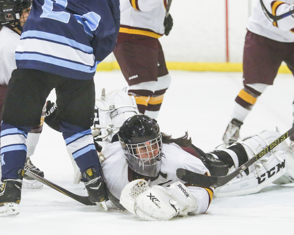 Cape Elizabeth goalie Abby Joy dives onto a York shot to make a save Friday during the 5-2 victory against York in a schoolgirl hockey opener at Troubh Arena.