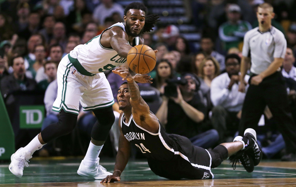 Brooklyn Nets guard Rondae Hollis-Jefferson reaches up as he loses control of the ball next to Celtics forward Jae Crowder in the first quarter of Friday night's game in Boston. Crowder scored 19 points in the Celtics' 120-95 win.