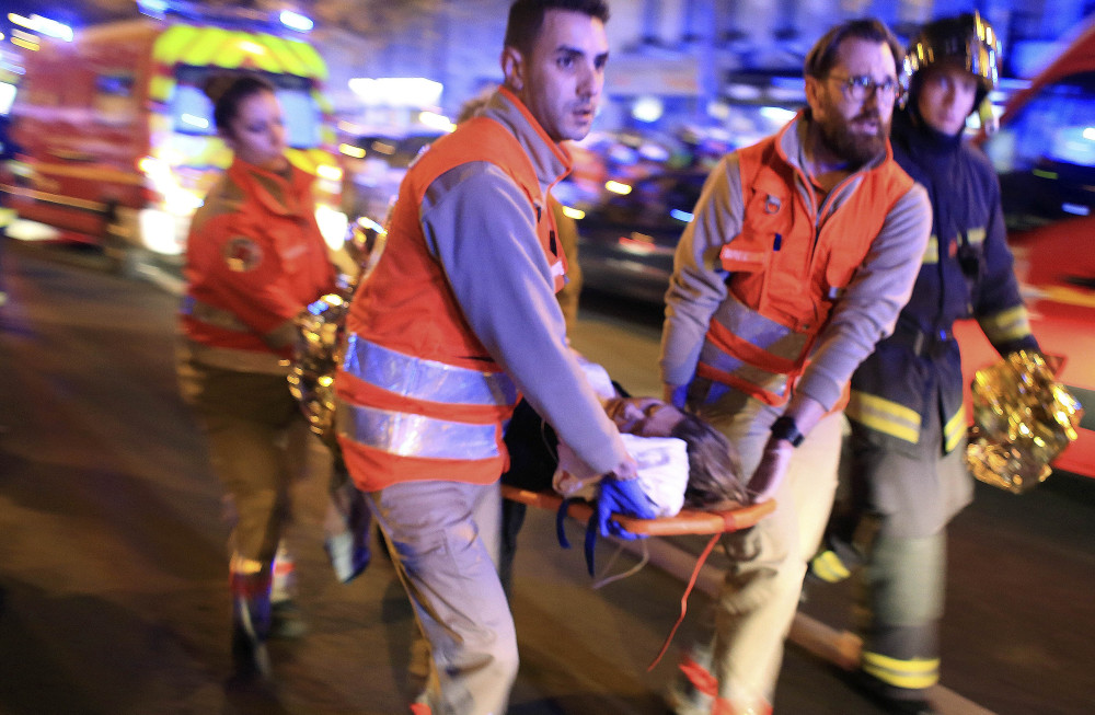 A woman is evacuated after the Nov. 13 attack in Paris. As of Wednesday, 195 people were still hospitalized.
