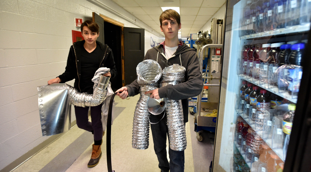Alan Baez, left, and Austin Witham carry sections of the Tin Man costume to the dressing area at Trask Auditorium.