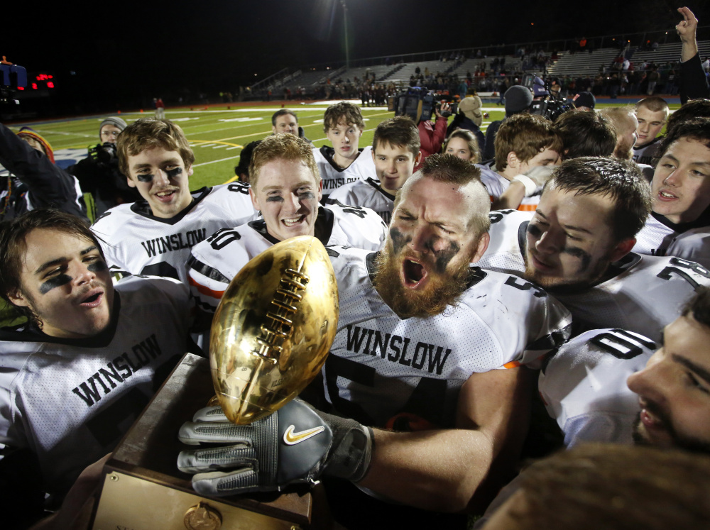 Alex Clark, a four-year starter, hoists the Gold Ball as he and his Winslow teammates celebrate another Class C state championship.