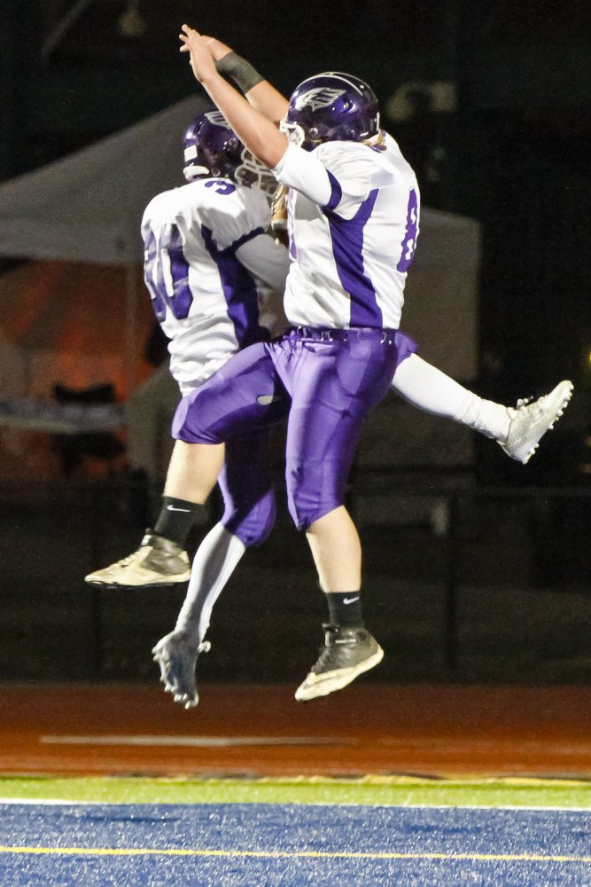 Zach Doyon, left, and Chris Sarzynski of Marshwood celebrate in the end zone after Doyon caught a touchdown pass during the 21-14 victory against Brunswick in the Class B state final at Fitzpatrick Stadium.