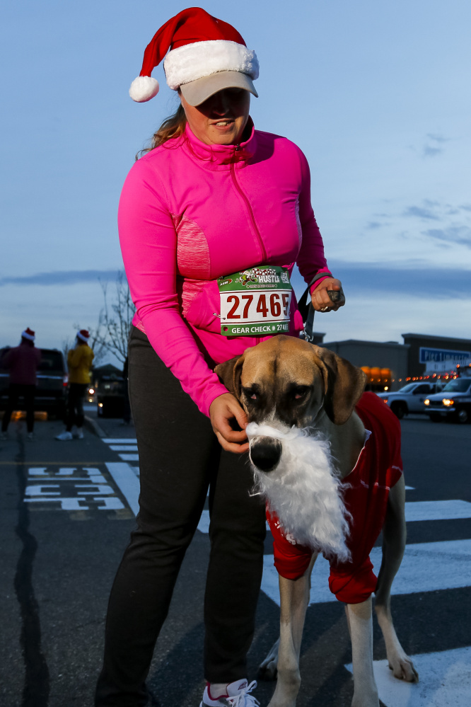 SOUTH PORTLAND, ME - NOVEMBER 22: Tina Chadbourne, of Bucksport, adjusts a fake beard on Wilson -- a 7-month-old Great Dane -- minutes before the running of the annual Santa Hustle Half Marathon and 5K on Sunday at the Maine Mall. (Photo by Ben McCanna/Staff Photographer)