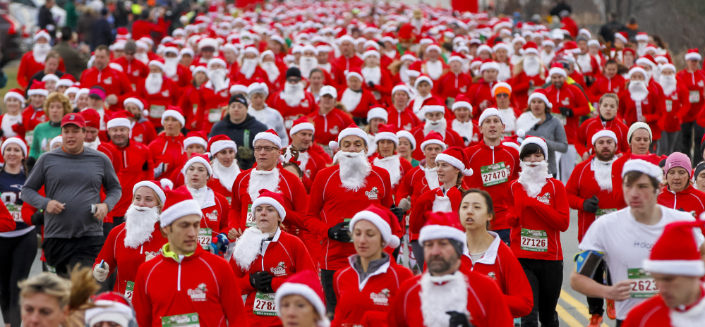 A pack of Santas begins the 5K in the Santa Hustle New England 5K and Half Marathon on Sunday at the Maine Mall.