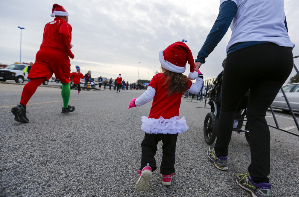 Evelyn Scherb, 2, of South Portland, holds her mother's hand near the finish line for the annual Santa Hustle Half Marathon and 5K on Sunday at the Maine Mall. Jessica Scherb said her daughter walked the last quarter mile of the 5K, but rode in a stroller for most of the way.