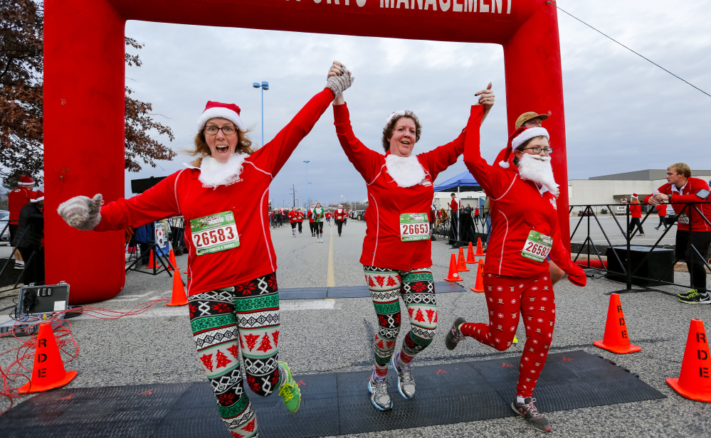 Carrie Castonguay, from left, Marjorie Fletcher and Catherine Castonguay join hands as they cross the finish line at the annual Santa Hustle Half Marathon and 5K on Sunday at the Maine Mall. The trio finished the 5K with a time of 34:49.