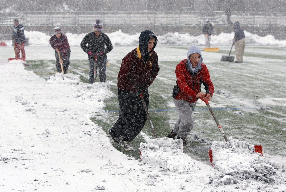 Crews at Montini High School work to remove snow from the field before the Class 6A semifinal high school football game against Prairie Ridge in Lombard, Ill., on Saturday.