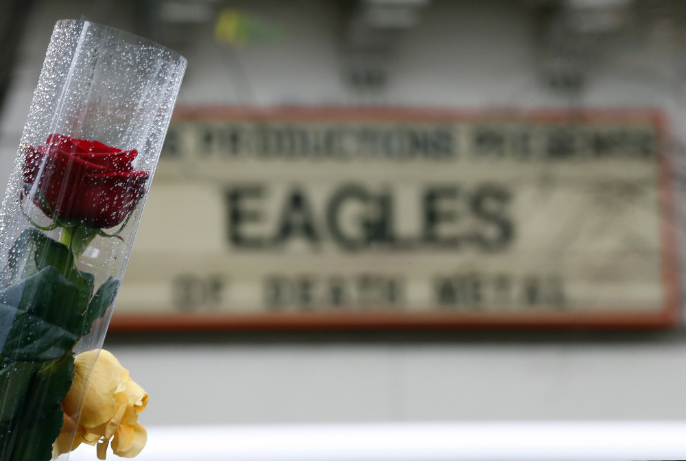 A rose is placed in front of an advertising board for the music band The Eagles of Death Metal, which was playing a concert when gunmen attacked Nov. 13 at the Bataclan concert hall in Paris.
